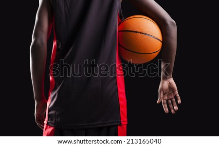 Rear view of a basketball player standing with a basket ball on black background - stock photo