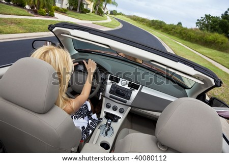 Rear view of a beautiful young blond woman driving her convertible car - stock photo