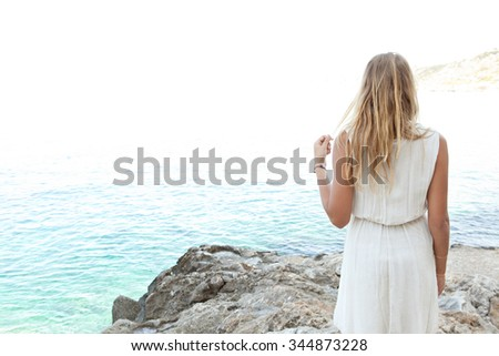 Rear view of a beautiful young blond woman standing on a rocky beach contemplating the blue sea on a summer holiday, relaxing nature outdoors. Travel and relaxing lifestyle. Serene adolescent space. - stock photo