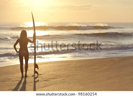 Rear view of a beautiful young woman surfer girl in bikini with surfboard at a beach at sunset or sunrise - stock photo