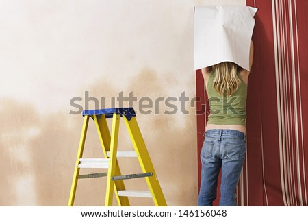 Rear view of a blond young woman hanging wallpaper - stock photo