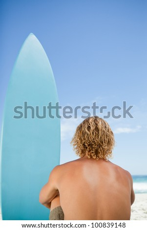 Rear view of a blonde man waiting for a wave while sitting next to his surfboard - stock photo