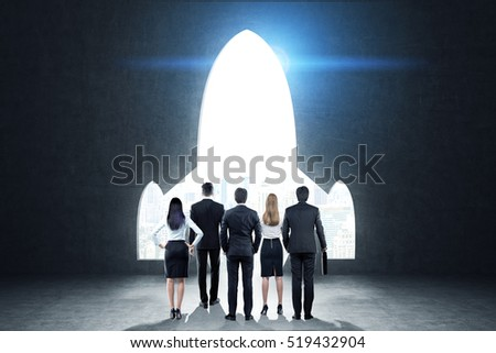 Rear view of a business team standing near black wall with a plane shaped opening in it. Blue light. Concept of project launching. Toned image