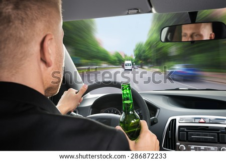Rear View Of A Businessman Drinking Beer While Driving Car
