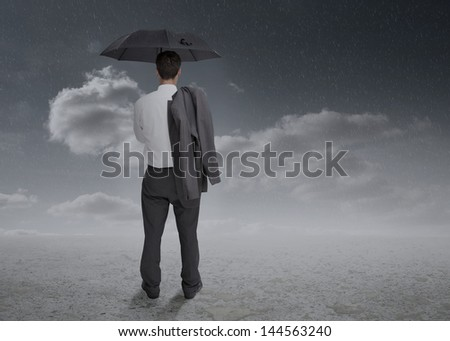 Rear view of a businessman holding an umbrella and a jacket over his shoulder