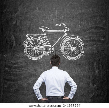 Rear view of a businessman in formal clothes who is looking at the huge black chalkboard with a drawn sketch of a bicycle. A concept of environmental friendly ways of commuting and travelling. - stock photo