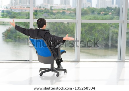 Rear view of a businessman sitting on a chair with opened hands to the nature - stock photo