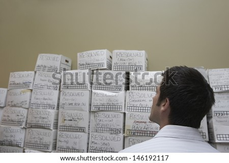 Rear view of a businessman standing in front of stack of filing boxes in storage room