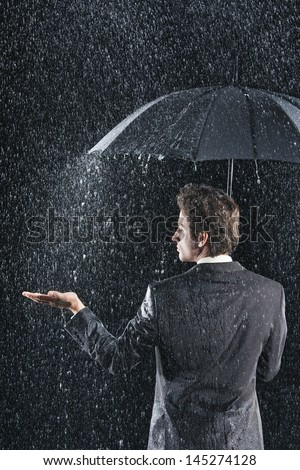 Rear view of a businessman sticking hand out from under umbrella to feel the rain - stock photo