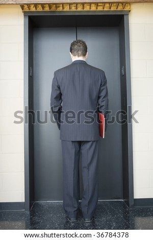 Rear view of a businessman waiting for the elevator in an office building - stock photo