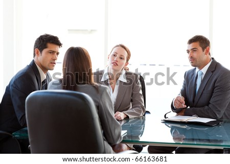 Rear view of a businesswoman being interviewed by three executives sitting around a table