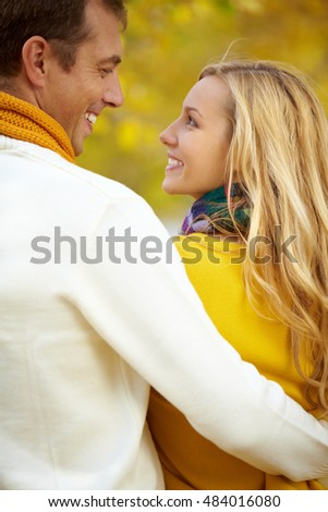 Rear view of a couple embracing, looking at each other and smiling
