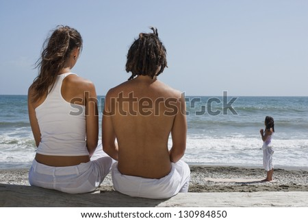 Rear view of a couple looking at a woman doing yoga on the beach