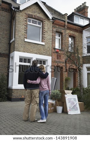 Rear view of a couple looking at house with possessions outside - stock photo