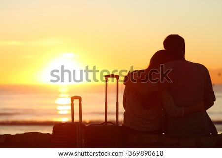 Rear view of a couple silhouette of tourists outside with suitcases on vacations enjoying watching the sun in the background on the beach at sunset - stock photo