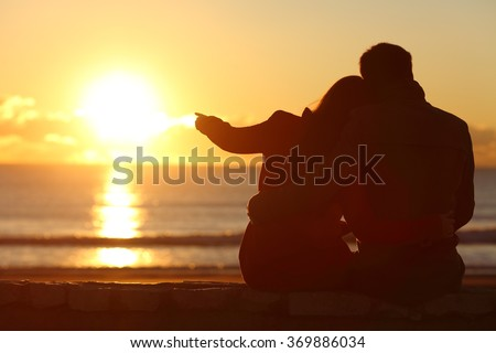 Rear view of a couple silhouette sitting cuddling and enjoying pointing at sun at sunset outside on the beach in winter - stock photo