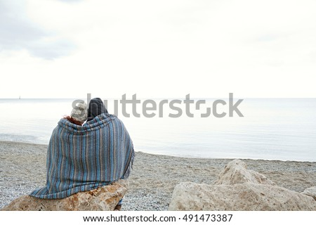 Rear view of a couple sitting on rocks of natural beach wrapped up sharing a blanket on a cold winter vacation, outdoors space. Boyfriend and girlfriend travel lifestyle, serenity and contemplation.