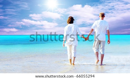 Rear view of a couple walking on the beach, holding hands. - stock photo