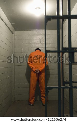 Rear view of a criminal standing in jail - stock photo