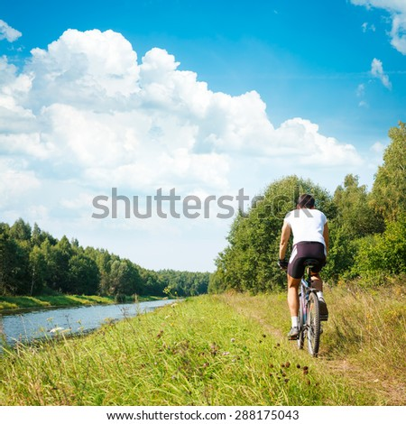 Rear View of a Cyclist Riding a Bike on River Bank. Healthy Lifestyle Concept. Square Photo with Copy Space.