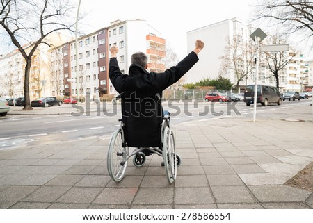 Rear View Of A Disabled Man On Wheelchair With Hand Raised - stock photo
