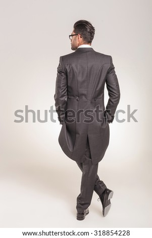 Rear view of a elegant young business man standing with his hands in pockets on studio background. - stock photo