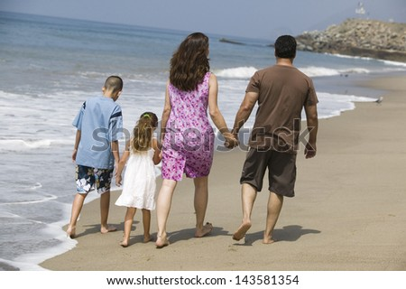 Rear view of a family holding hands and walking at water's edge on the beach - stock photo