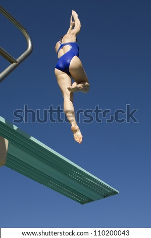 Rear view of a female diver diving of the springboard