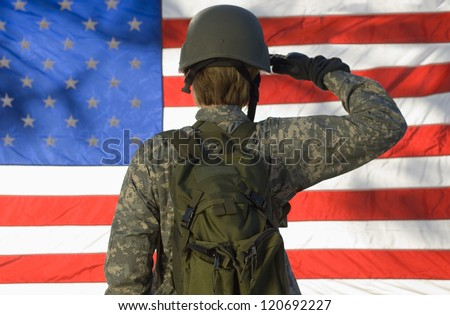 Rear view of a female soldier saluting American flag