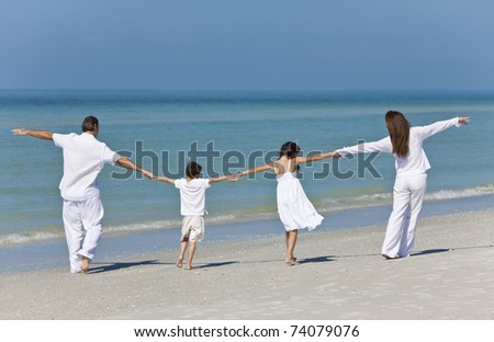 Rear view of a happy family of mother, father and two children, son and daughter, running holding hands and having fun in the sand of a sunny beach - stock photo