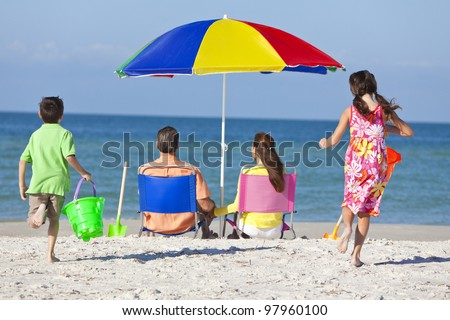 Rear view of a happy family of mother & father, parents daughter & son children having fun in deckchairs under an umbrella on a sunny beach