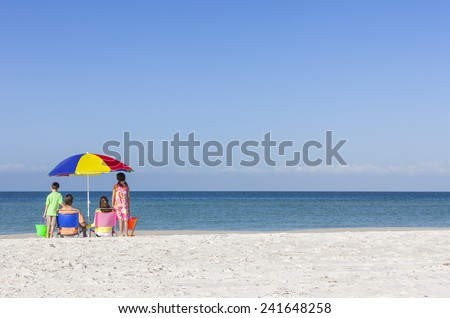 Rear view of a happy family of mother & father, parents daughter & son children sitting in deckchairs under an umbrella on a deserted sunny beach - stock photo