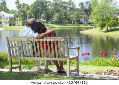 Rear view of a happy romantic senior African American couple sitting on a park bench embracing looking at a lake - stock photo