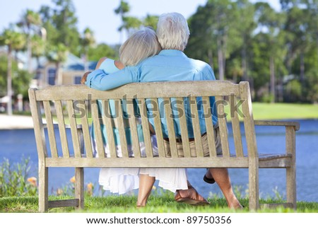Rear view of a happy romantic senior couple sitting on a park bench embracing looking at a blue lake - stock photo
