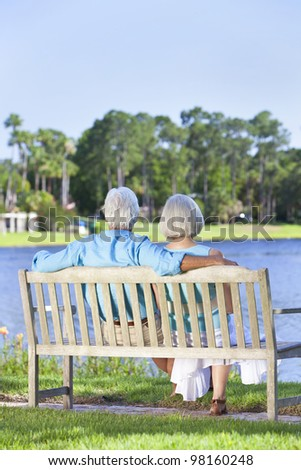 Rear view of a happy romantic senior couple sitting on a park bench looking at a blue lake - stock photo