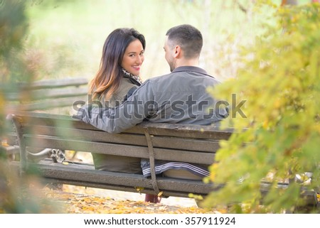Rear view of a happy young couple sitting on a park bench, young woman looking to camera over the shoulder while her boyfriend is looking at her - stock photo