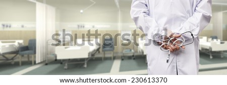 rear view of a male doctor with stethoscope in hospital ward. - stock photo