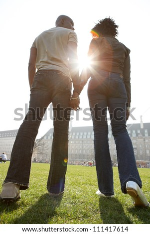 Rear view of a man and woman's figures holding hands while walking through London city on a sunny day. - stock photo