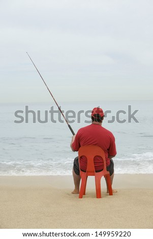 Rear view of a man in red tshirt sitting on red plastic chair and fishing at beach - stock photo
