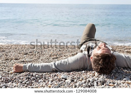Rear view of a man laying down on the shore a white pebbles beach during a sunny day in winter with the blue sea. - stock photo