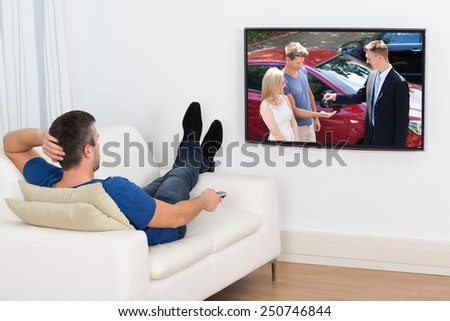 Rear View Of A Man Lying On Couch Watching Television - stock photo