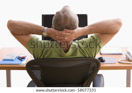 Rear view of a man seated at a desk in front of a laptop. He is sitting back in his chair with his hands behind his head. Horizontal shot.