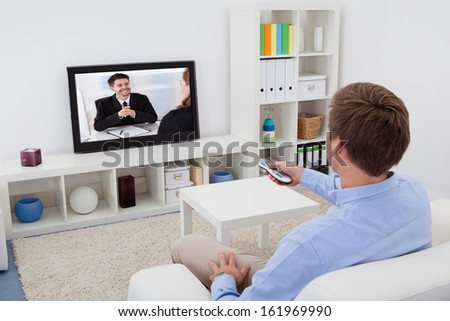 Rear View Of A Man Sitting On Couch Watching Television