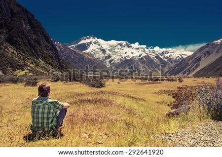 Rear view of a man sitting on grass and looking at mountains and glacier - stock photo