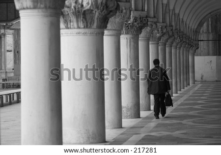 Rear view of a man walking in a corridor with pillars, Venice, Italy (black and white), October 2000