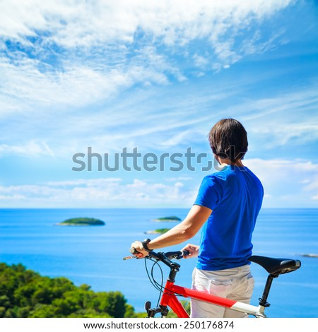 Rear View of a Man with a Bicycle on Summer Sea Background. Healthy Lifestyle and Travel Concept. Copy Space. - stock photo