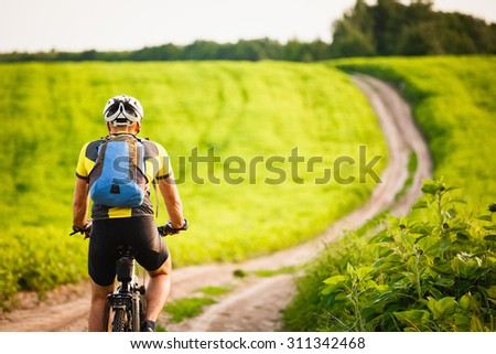 Rear View of a Man with Backpack Riding a Bicycle on Beautiful Nature Background. Healthy Lifestyle and Travel Concept. - stock photo