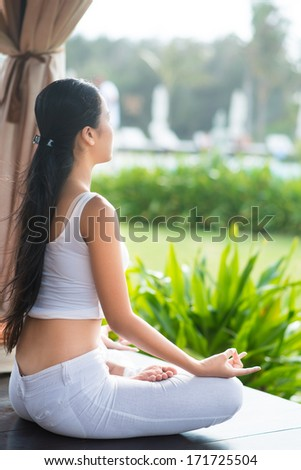 Rear view of a meditating girl - stock photo