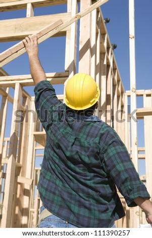Rear view of a middle aged foreman working at a construction site