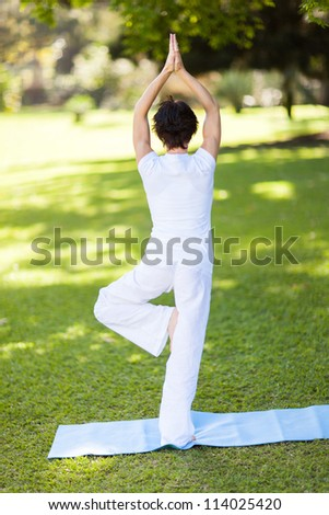 rear view of a middle aged woman doing yoga outdoors - stock photo